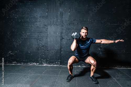 plakat Young strong fit muscular sweaty man with big muscles strength cross workout training with dumbbells weights in the gym dark image with shadows real people