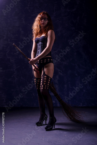 Tablou Canvas Sexy woman in a corset, stockings and with a broom posing on a dark background