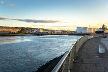 Commercial Port With Huge Fuel Tanks As Seen From The Footpath Along The Harbour Mouth At Sunset. Aberdeen, Scotland, UK.
