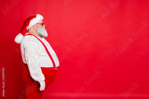 Fototapeta Profile side photo of white gray hair fat overweight santa claus with big funny belly abdomen ready for new year festival event wear overalls eyeglasses isolated over red background obraz