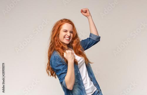 Millennial Girl Shaking Fists Celebrating Success On Light Studio Background Fototapeta