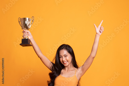 Successful number one winner young asian woman holding a trophy. Canvas Print