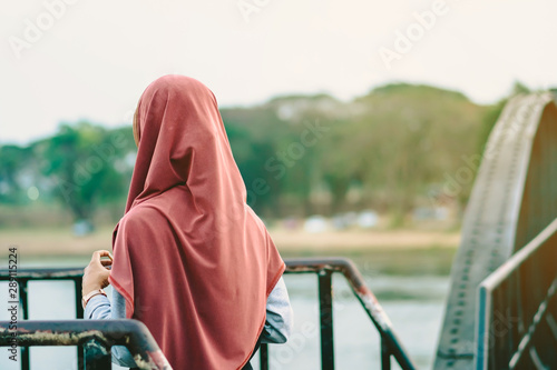 Fotomural  Back view of Muslim woman relax and admire the beautiful scenery in the evening on The Bridge of the River Kwai in Kanchanaburi, Thailand