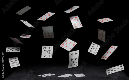Photo playing cards fall on a black table