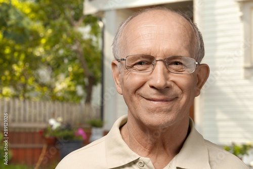 Handsome senior man standing on the house background
