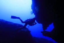 宮古島市下地島にあるダイビングスポットの海底洞窟の女王の部屋で泳ぐダイバー