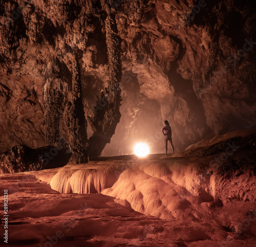 Photo sur Aluminium Bordeaux Young woman inside the Nguom Ngao limestone cave in North Vietnam, Cao Bang province. Enormous stalagmites and stalactites. Cao bang province.