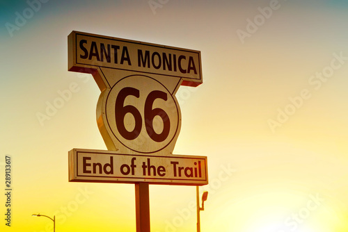 Road sign of route 66 as the terminus on Santa Monica beach at sunset Wallpaper Mural