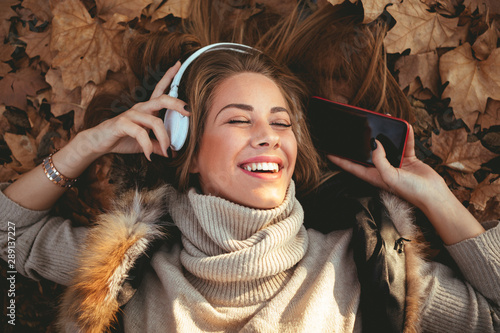 Young woman lying in the leaves and listening to music - 289137227