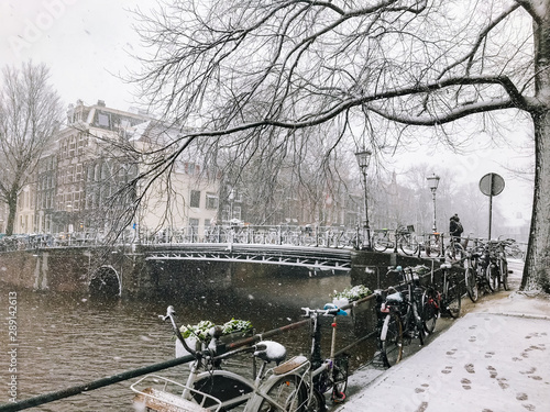 Snowy bicycles on the bridge in the city center Amsterdam Netherlands. Blizzard on winter in the Netherlands. Bicycles covered with snow on a bridge. Snowfall in capital Netherlands #289142613