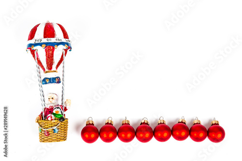 Santa Claus in Hot air balloon flight with red balls decoration on white background - 289149628