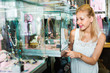 Portrait of young woman standing next to glass showcases