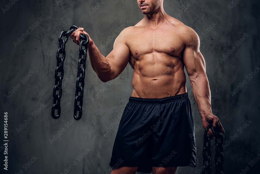 Fototapety, obrazy: Pensive strong bodybuilder is posing for photographer at studio with chains in his hands.