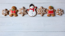 Christmas Wooden Background With Gingerbread Snowflakes, Gingerbread Men And Snowman.