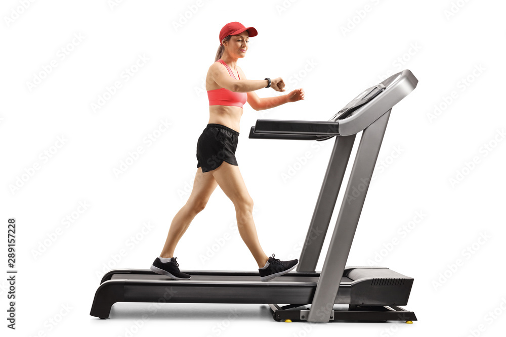 Fototapety, obrazy: Young woman on a treadmill walking and checking her smart sports bracelet
