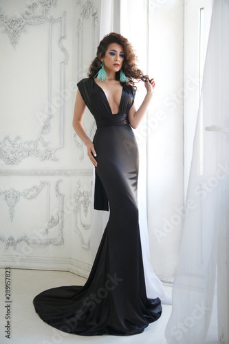 Portrait of an elegant brunette girl with magnificent curls in a black long evening dress in full growth Wallpaper Mural