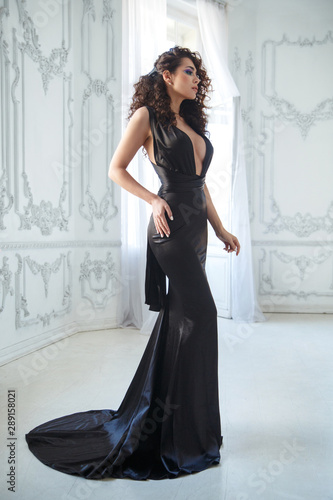 Photo Portrait of an elegant brunette girl with magnificent curls in a black long evening dress in full growth