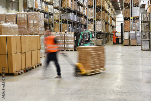 Fotomural  warehouse worker in a forwarding agency - interior with forklift - transport and