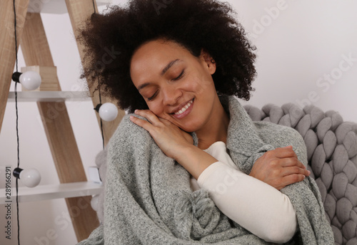 Fotografia Cozy Woman covered with soft merino blanket daydreaming and relaxing at home