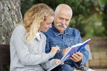 Senior Dad And Daughter Reading In Te Park