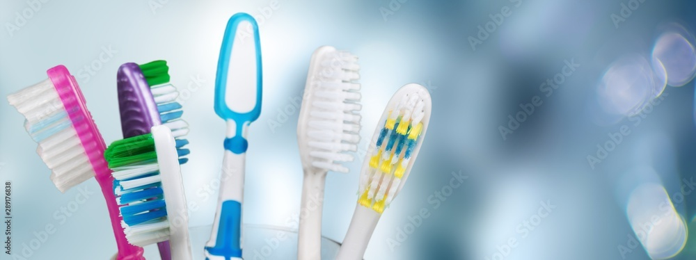 Fototapety, obrazy: New Colorful Toothbrushes in A Glass  on  Background