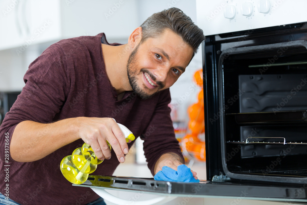 Fototapety, obrazy: portrait of man spraying product to clean oven