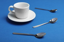 Teaspoons And Cup With Saucer On Blue Background