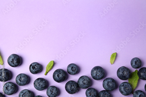 Fotografia Tasty ripe blueberries and leaves on violet background, flat lay with space for