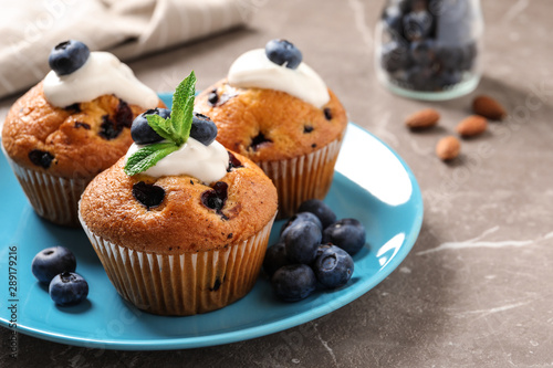 Obraz na plátně  Plate of tasty muffins and blueberries on marble table