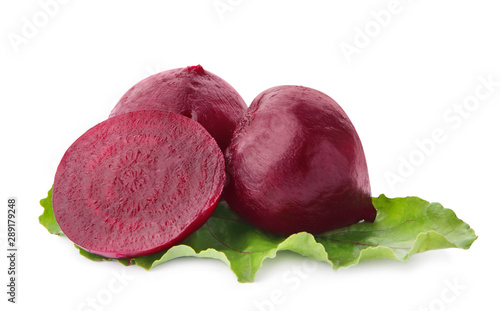 Fototapeta  Whole and cut boiled red beets with green leaf on white background
