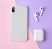 Wireless Earphones, Mobile Phone And Charging Case On Color Background, Flat Lay