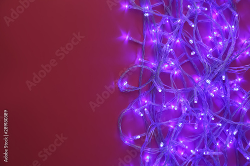 canvas print motiv - New Africa : Glowing Christmas lights on burgundy background, top view. Space for text