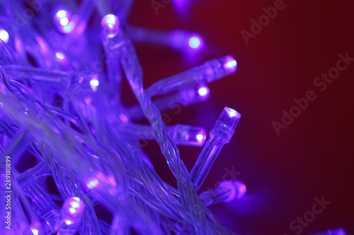 canvas print motiv - New Africa : Glowing Christmas lights on dark red  background, closeup
