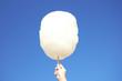 Leinwanddruck Bild - Woman holding white cotton candy against blue sky