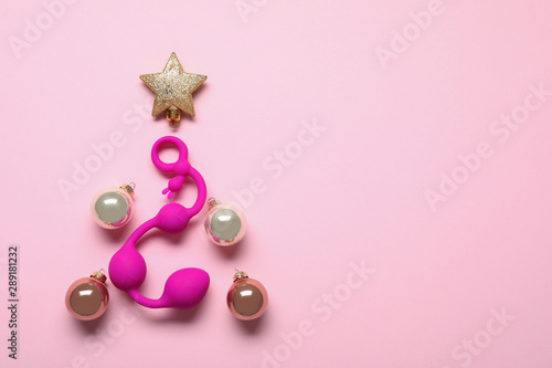 Obraz na plátně  Christmas tree made with decorative balls, star and sex toy on pink background, flat lay