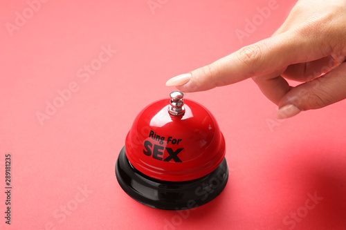 Photo Young woman with sex bell on red background, closeup