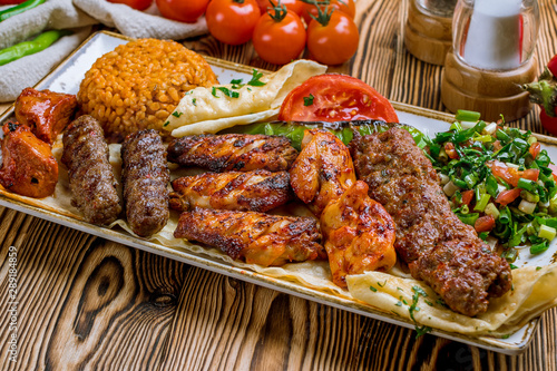 Photo assorted kebabs with bulgur and vegetables Turkish cuisine on wooden table