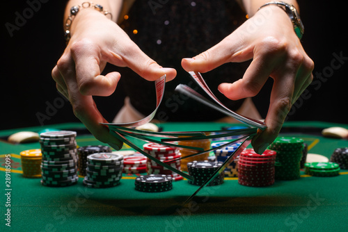 Obraz na płótnie Girl dealer or croupier shuffles poker cards in a casino on the background of a table, chips,
