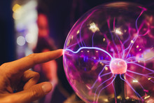 Hand Touching A Plasma Ball With Smooth Magenta-blue Flames.