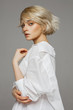 Portrait of beautiful blonde woman in white shirt and fashionable hair