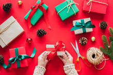 Hand Holding Gift/presents Box Over Red Background For Chirstmas And Happy New Year Concept. Topview Flatlay