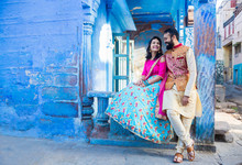 Asian Indian Couple Sitting Together Wearing Traditional Ethnic Dress Looking At Each Other Happily Before Wedding Day In Blue House In The Background, City Of Jodhpur