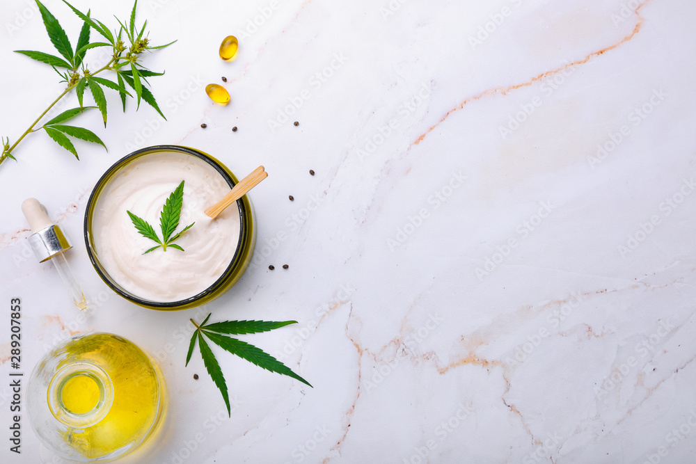 Fototapety, obrazy: Bank of medical cream with CBD oil, hemp leaf on a marble table. Flat lay, top view.