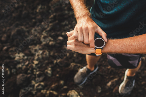 Vászonkép  Young athletic man using fitness tracker or smart watch before run training outdoors