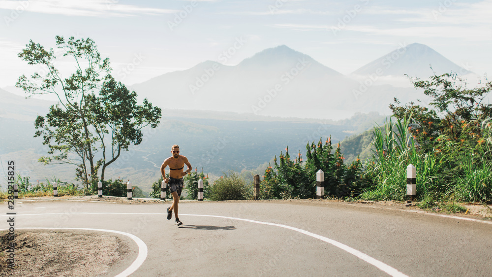 Fototapety, obrazy: Man running topless in uphill on the asphalt road in hot summer weather. Panoramic mountain view on background. Using chest heart rate monitor.