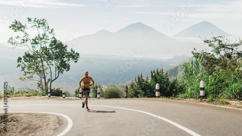 Man running topless in uphill on the asphalt road in hot summer weather. Panoramic mountain view on background. Using chest heart rate monitor.