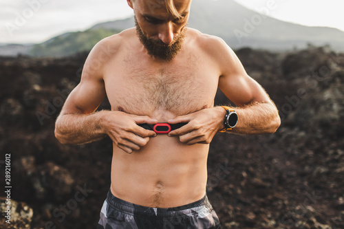 Valokuvatapetti Male runner wearing professional chest heart rate monitor and preparing for trail running outdoors