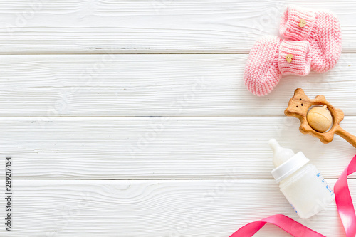 Fotografía  Booties for newborn girl with rattle and bottle on white wooden background top v