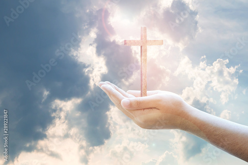 Fotomural Human hands holding wooden cross against the light from cloudy blue sky, Christi