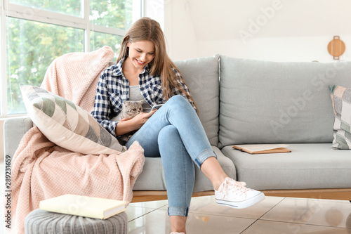 Obraz Beautiful young woman with cute cat and mobile phone at home - fototapety do salonu